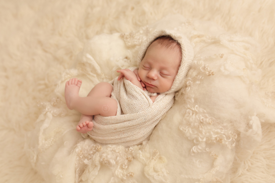 Newborn baby takes his professional pictures wearing a cream bonnet and wrap.