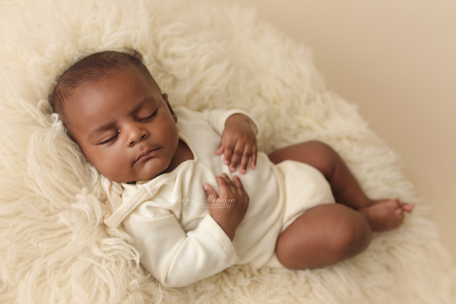 3 month old sleeps during his sleepy baby pictures on cream or ivory colored flokati at Waukesha county portrait studio.